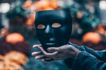 Masque noir porté par des mains